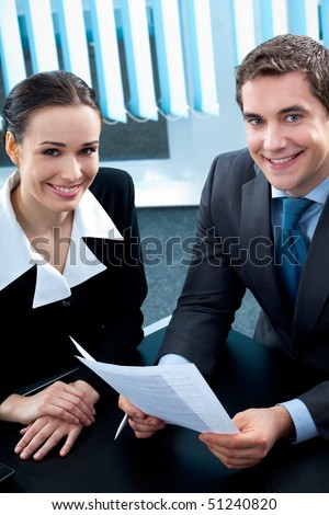 Businesspeople or business person and client, with document at office - stock photo