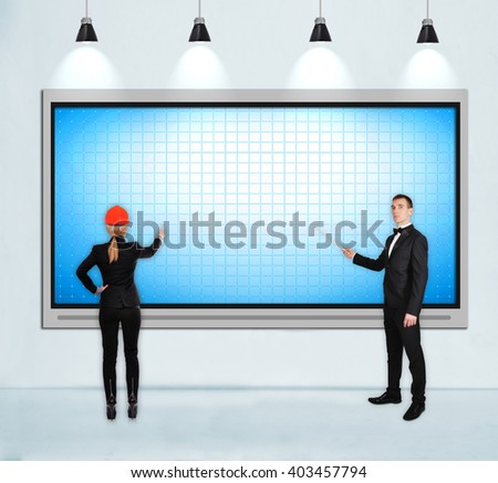 businesspeople pointing to blank tv screen on concrete wall in loft room - stock photo