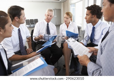 Businesspeople Seated In Circle At Company Seminar - stock photo