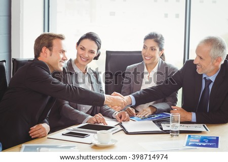 Businesspeople shaking hands in conference room during meeting - stock photo