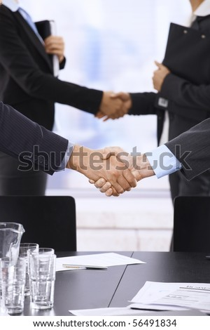 Businesspeople shaking hands in skyscraper office on meeting.