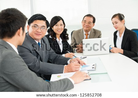Businesspeople sitting and talking at meeting - stock photo
