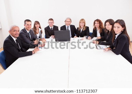 Businesspeople Sitting At Conference Table At The Meeting