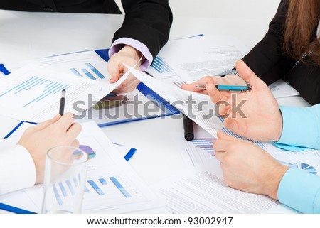 Businesspeople sitting at desk working in team together with documents sign up contract, businessmen holding financial charts, graph, folder with papers, explain business plan - stock photo