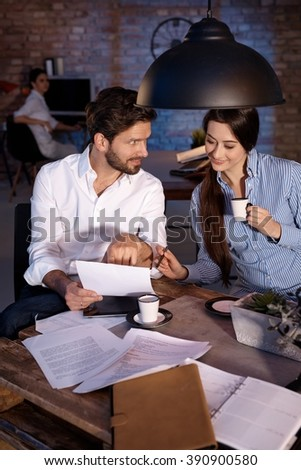 Businesspeople sitting at desk, working together, drinking coffee, smiling. - stock photo