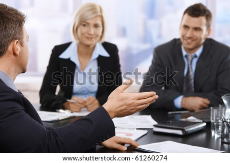 Businesspeople sitting at meeting table discussing work. Focus on hand.? - stock photo
