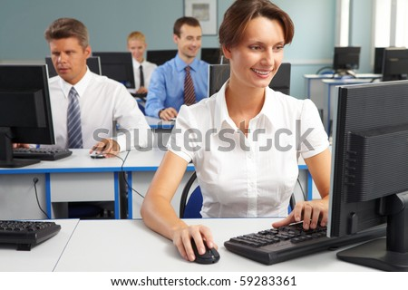 Businesspeople sitting at tables and looking at their monitors with smiling woman at foreground - stock photo