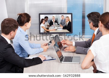 Businesspeople Sitting In A Conference Room Looking At Computer Screen - stock photo