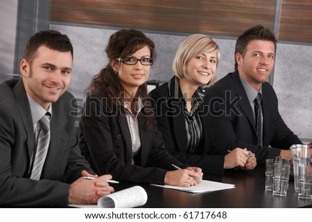 Businesspeople sitting in a row at meeting table in office, looking at camera, smiling.? - stock photo