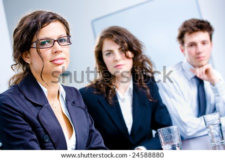 Businesspeople sitting in a row on a meeting at office.