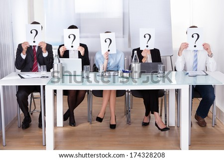 Businesspeople Sitting In Conference Room Holding Question Mark In Front Of Face - stock photo