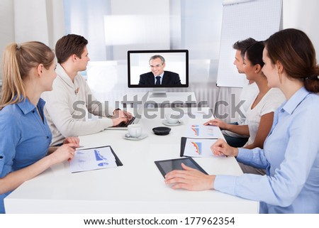 Businesspeople Sitting In Conference Room Looking At Monitor - stock photo