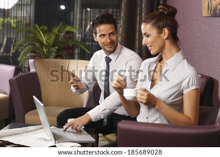 Businesspeople sitting on couch at hotel lobby or bar, working on laptop computer at late night, businesswoman having coffee.