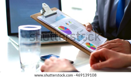 Businesspeople sitting on the desk on office