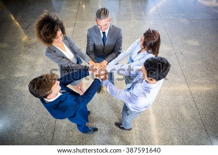 Businesspeople standing with their hands stacked in office - stock photo