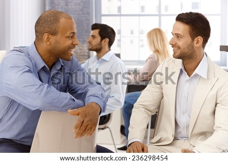 Businesspeople talking in office, smiling. - stock photo