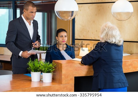 Businesspeople talking to receptionist in modern office - stock photo