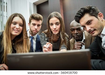 Businesspeople, teamwork. Group of multiethnic busy people looking at a laptop computer - stock photo
