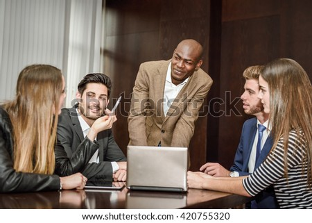 Businesspeople, teamwork. Group of multiethnic busy people working in an office - stock photo