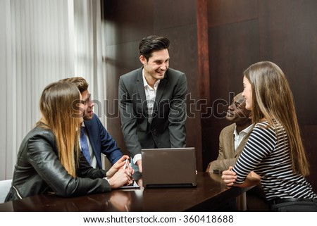 Businesspeople, teamwork. Group of multiethnic busy people working in an office. Male as leader wearing blazer jacket. - stock photo