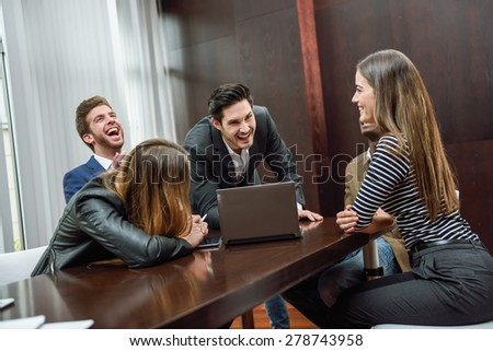 Businesspeople, teamwork. Group of multiethnic people laughing in an informal meeting in an office - stock photo