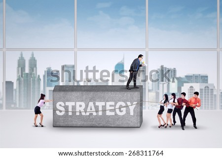 Businesspeople use a strategy and try to move an obstacle with a text of strategy - stock photo