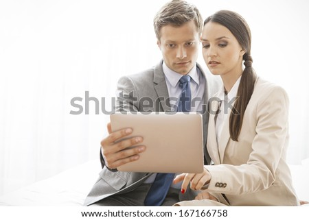 Businesspeople using digital tablet in hotel - stock photo