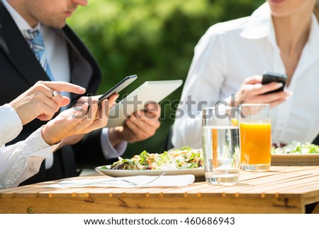 Businesspeople Using Mobile Phone With Food And Glass Of Juice On Table