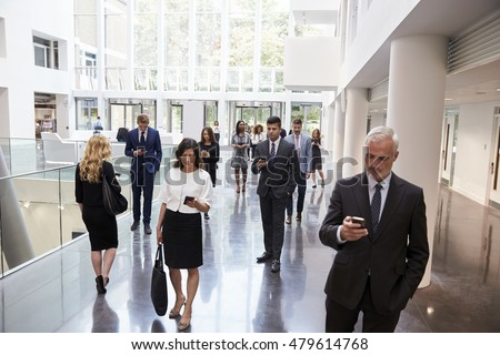 Businesspeople Using Technology In Busy Lobby Area Of Office