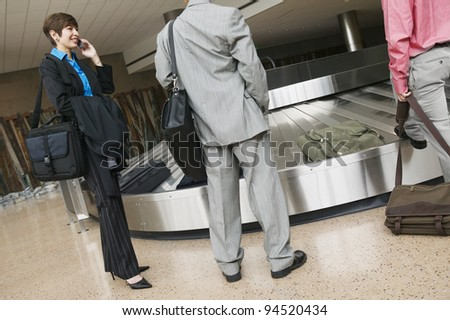 Businesspeople waiting for luggage at airport - stock photo