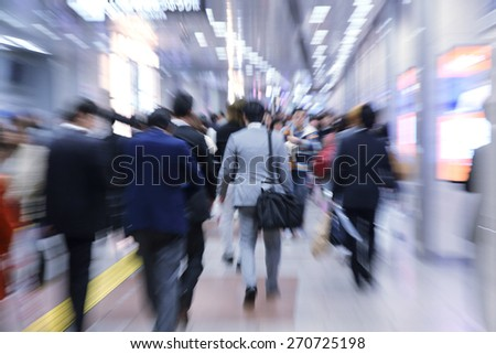 businesspeople walking in motion blur in a corridor