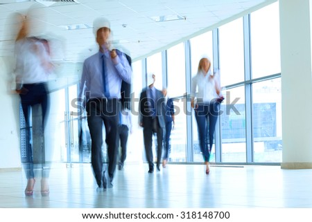 businesspeople walking in the corridor of an business center - stock photo