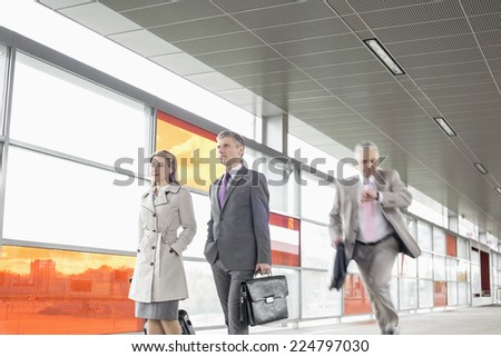Businesspeople walking while male colleague running in railroad station - stock photo