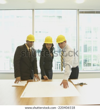 Businesspeople wearing hard hats and looking at blueprints in office - stock photo