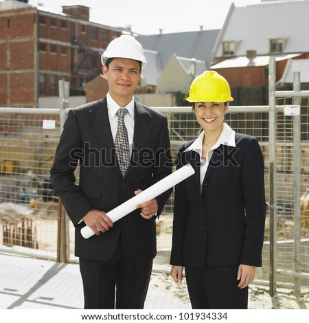 Businesspeople wearing hard hats at construction site - stock photo