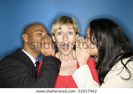 Businesspeople whispering into each ear of businesswoman as she looks shocked. - stock photo