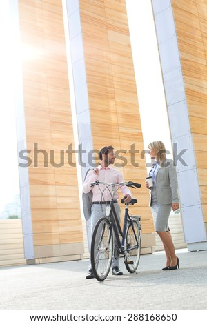 Businesspeople with bicycle conversing outside building - stock photo
