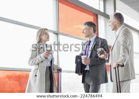 Businesspeople with coffee cups talking on railroad platform - stock photo