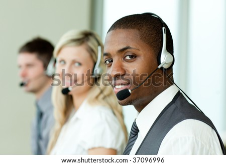 Businesspeople with headsets smiling at the camera at work