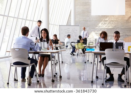Businesspeople Working At Desks In Modern Office