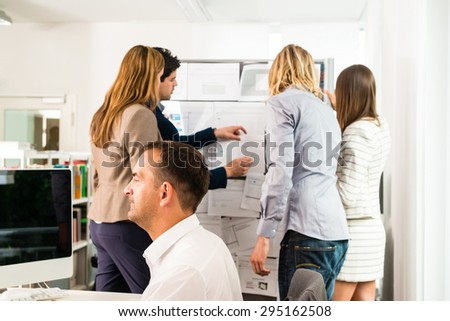 Businesspeople working in the office - some of them looking at bulletin board and discussing designs pinned at it, another guy in the front is working with several computer screens. Mixed caucasian