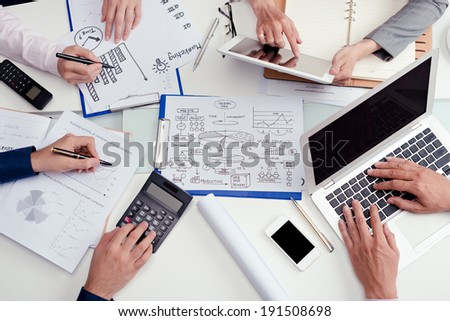 Businesspeople working on report - stock photo
