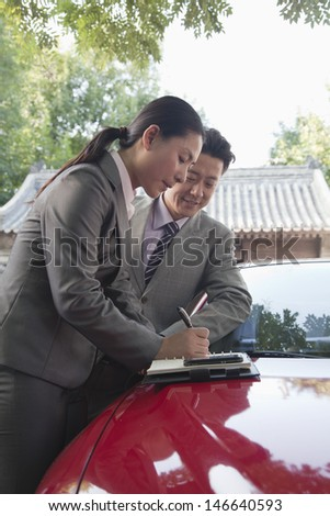 Businesspeople Working Outdoors on the Hood of a Car