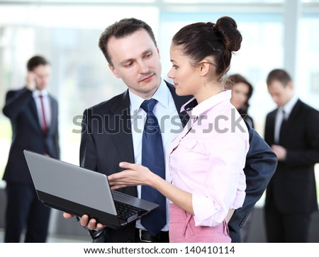Businesspeople working with laptop at office - stock photo