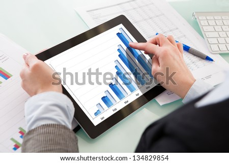 Businessperson Analyzing Graph On Digital Tablet In The Office - stock photo