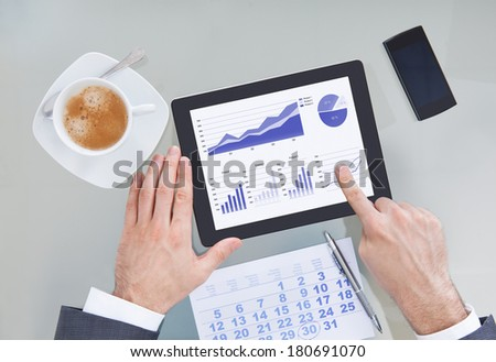 Businessperson Hand Holding Digital Tablet Showing Graph Diagram With Calendar - stock photo