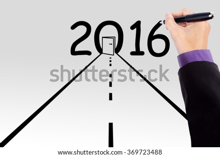 Businessperson hand using a pen to make a road with numbers 2016 and a door - stock photo