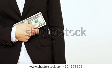 Businessperson in black suit holding a dollar bill isolated on white