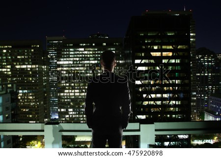 Businessperson on rooftop looking at illuminated night city. Research concept