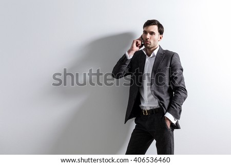 Businessperson standing against white wall talking on the phone. Mock up